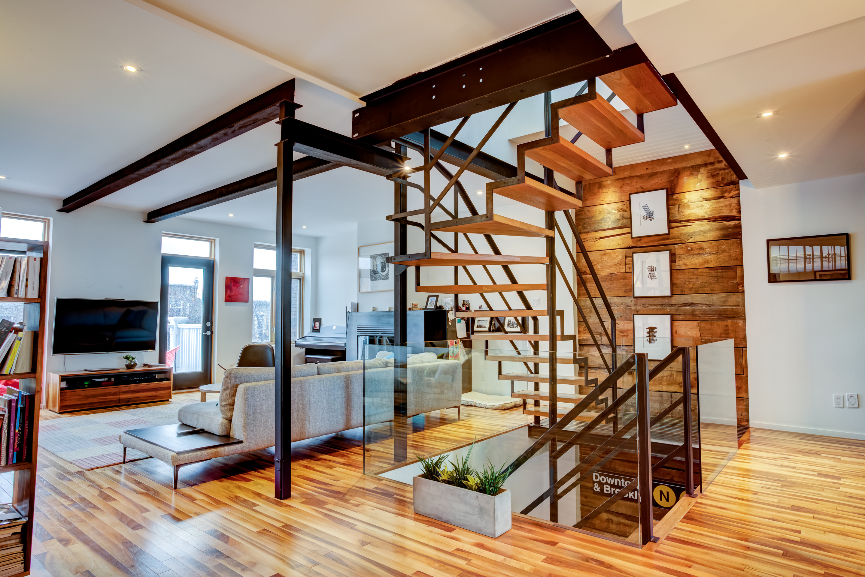 Construction of a wooden staircase with bright living room and raw beams