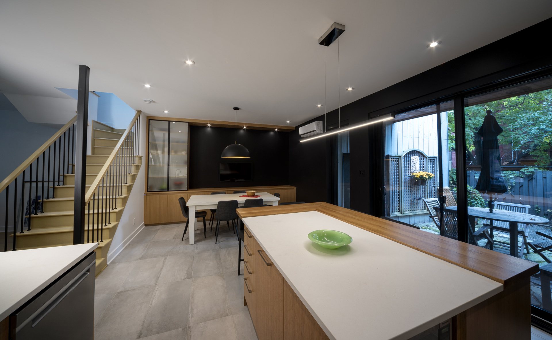 Modern kitchen with view on the terrace and dining room at the back of the room. A complete self-managed renovation
